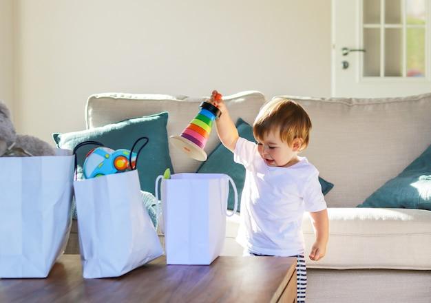 Leuke gelukkige smaling babyjongen die gifts speelgoed uit het winkelen zakken thuis uitpakken.