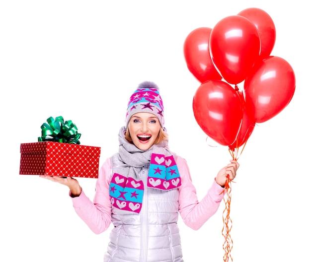 Leuke gelukkige volwassen vrouw met rode geschenkdoos en ballonnen geïsoleerd op wit
