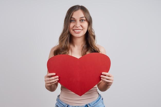 Leuke, gelukkige vrouw met een papieren hart, glimlachend.