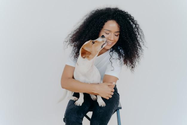 Leuke gelukkige vrouw met krullend haar krijgt kus van jack russell terrier voelt liefde voor favoriete huisdier plezier in gezelschap van hond