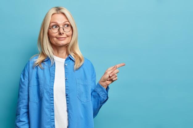 Leuke gerimpelde vrouw met blonde haarpunten op exemplaarruimte opzij