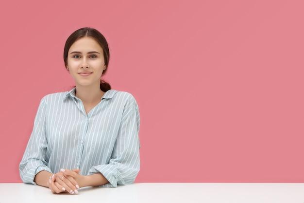 Leuke getalenteerde jonge vrouw in gestreept overhemd zit aan bureau met handen gevouwen tijdens sollicitatiegesprek, haar blik uiting van vertrouwen en bereidheid.