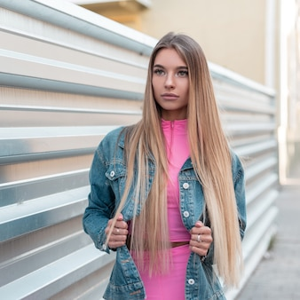 Leuke glamoureuze jonge vrouw met blond lang haar in een blauwe stijlvolle denim jasje in een trendy roze top in trendy roze korte broek vormt in de buurt van een zilveren hek. modieus mooi meisje in de stad. zomerstijl.