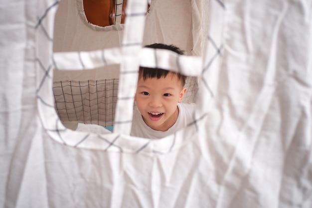 Leuke glimlachende aziatische schooljongen die pret het spelen in kinderentent of tipi thuis heeft