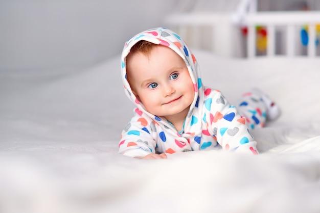 Leuke glimlachende baby in een modieuze hoodie die op een witte deken ligt