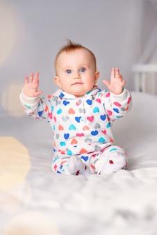 Leuke glimlachende baby in een modieuze hoodiezitting op een witte deken. kind lachen en opgeheven handen omhoog.
