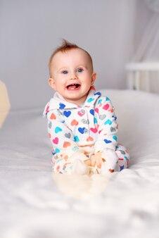 Leuke glimlachende baby in een modieuze hoodiezitting op een witte deken. kind lacht.