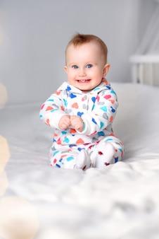 Leuke glimlachende baby in een modieuze hoodiezitting op een witte deken. spelen, lachend kind.