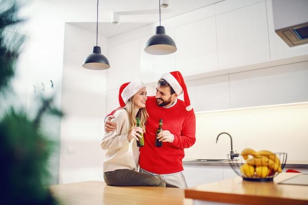 Leuke glimlachende blonde vrouwenzitting op keukenteller en bekijkend haar vriend