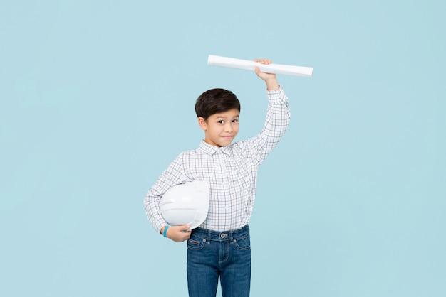 Leuke glimlachende jonge aziatische jongen met helm die toekomstige ingenieur streven te zijn die blauwdruk tonen die op lichtblauwe muur wordt geïsoleerd