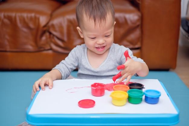 Leuke glimlachende kleine aziatische 18 maanden / 1 jaar oude peuter baby jongen kind vinger schilderen met handen en aquarellen, kind schilderen thuis, creatief spel voor peuters, montessori onderwijs concept
