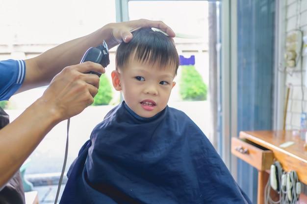 Leuke glimlachende kleine aziatische 3-4 jaar oude peuter jongenskind krijgt een knipbeurt bij de kapper van de kapper, kid knippen met kapper machine