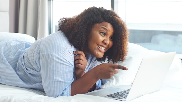 Leuke glimlachende mollige vrouw communiceert met vrienden via webcam op een laptop. zelfisolatie, coronavirusquarantaine