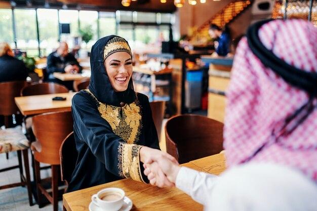 Leuke glimlachende positieve arabische vrouw gekleed in traditionele slijtage het schudden handen