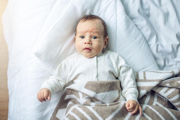 Leuke grappige baby die op een wit bed ligt dat met een deken wordt behandeld