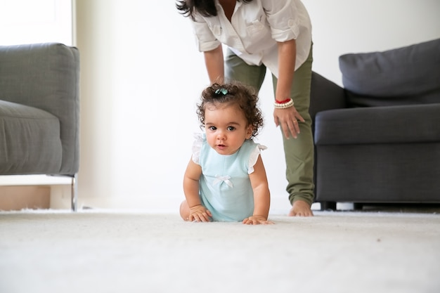 Leuke grappige baby die op vloer thuis kruipt. moeder die achter klein kind staat. ouderschap en jeugdconcept