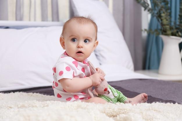 Leuke grappige baby met konijntjesstuk speelgoed thuis op bed zitten