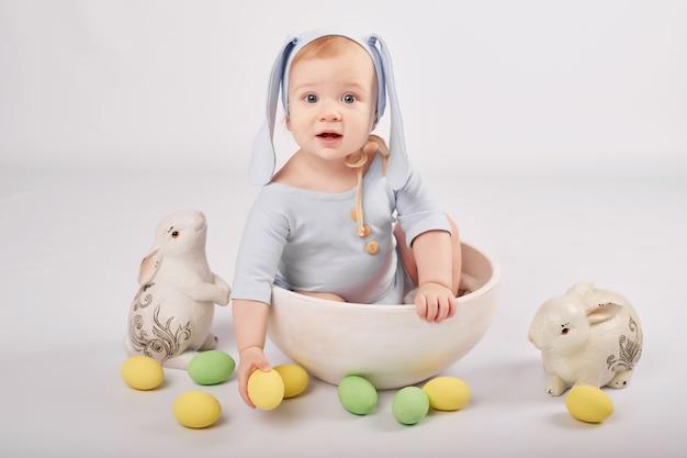 Leuke grappige babyjongen met konijntjesoren en kleurrijke paaseieren en konijnen. pasen baby. groet pasen kaartsjabloon.