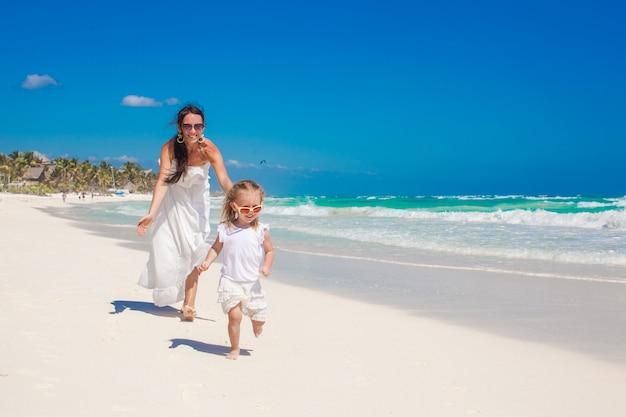 Leuke grappige dochter die pret met haar aardige jonge moeder op het witte zandige strand in mexico heeft