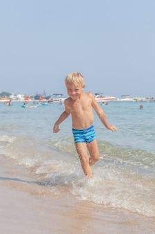 Leuke grappige gelukkige kleine jongen spelen in de golven van het water op zee oceaan op een zonnige dag