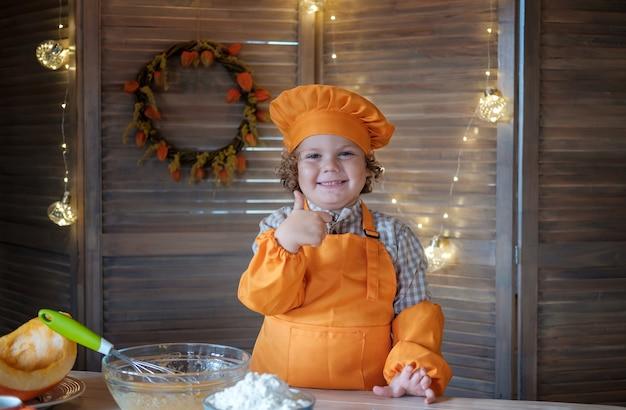 Leuke grappige jongen in een chef-kokkostuum toont een soortgelijk gebaar. kleine chef-kok in de keuken