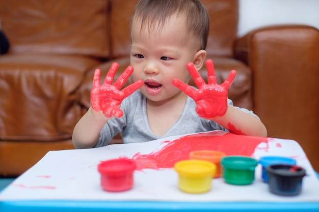 Leuke grappige kleine aziatische 18 maanden / 1 jaar oude peuter baby jongen kind vinger schilderen met handen en aquarellen, kind schilderen thuis, creatief spel voor peuters, montessori onderwijs concept