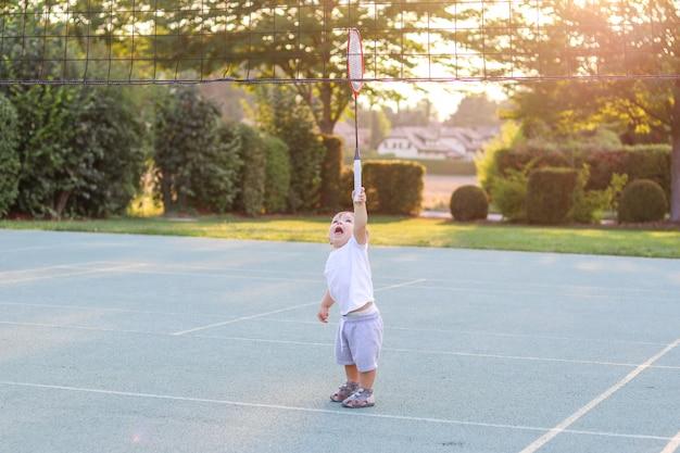 Leuke grappige kleine jongen die speelnet met badmintonracket probeert te bereiken.