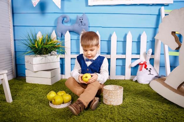 Leuke grappige kleine jongen met rieten mand. kid verzamelt herfst herfst oogst. gelukkig kind op de boerderij