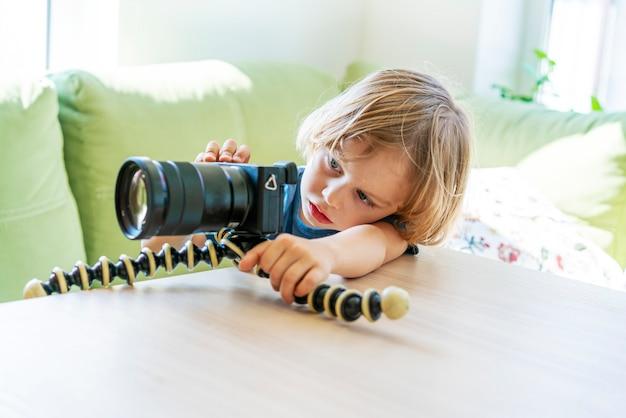Leuke grappige kleine jongen oefenen in het nemen van foto met camera op statief.