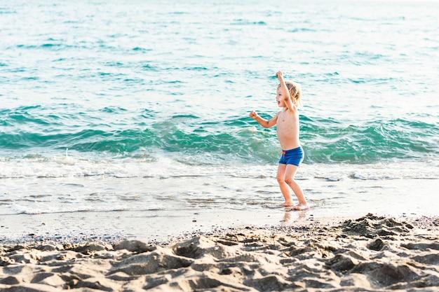 Leuke grappige kleine jongen spelen en plezier hebben aan zee zomer strandvakantie jeugd levensstijl...