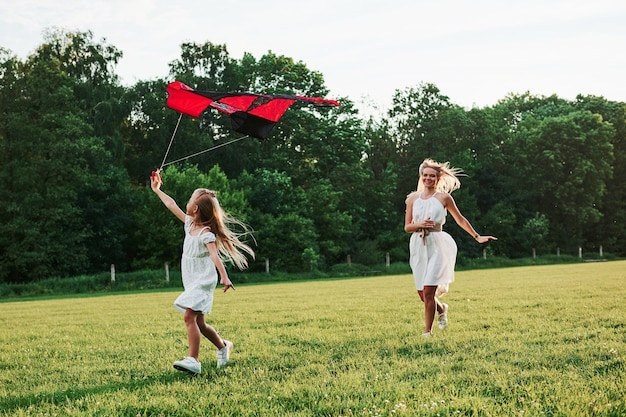 Leuke groene kleuren. moeder en dochter hebben plezier met vlieger in het veld. prachtige natuur.