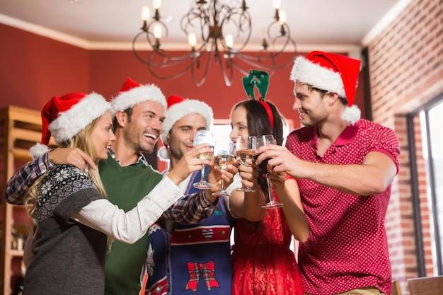 Leuke groep vrienden die met santahoeden roosteren