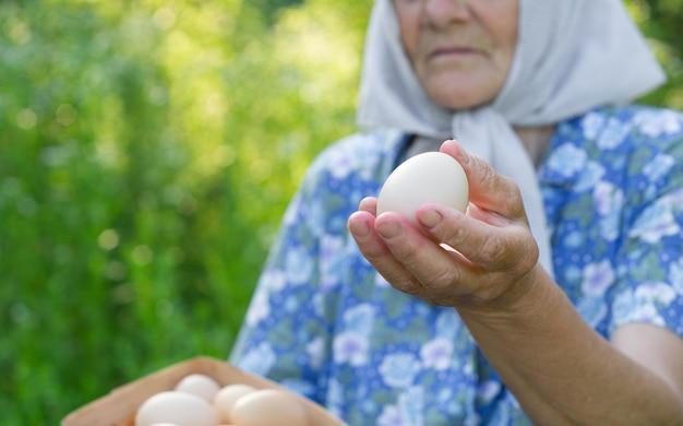 Leuke grootmoeder houdt een dienblad met eieren