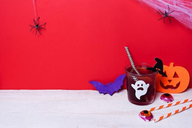Leuke halloween-drankjes met pompoen voor een kinderfeestje op wit hout met rode scène