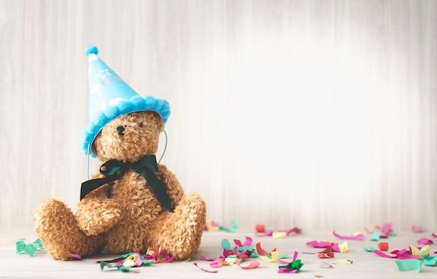Leuke harige bruine beer dragen hoed met vieren partij kleurrijke confetti op houten tafel
