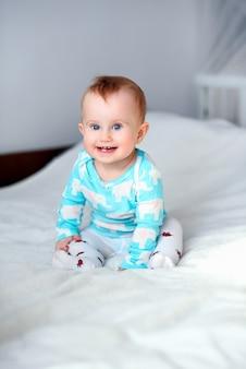 Leuke het glimlachen babyzitting op de witte deken op bed