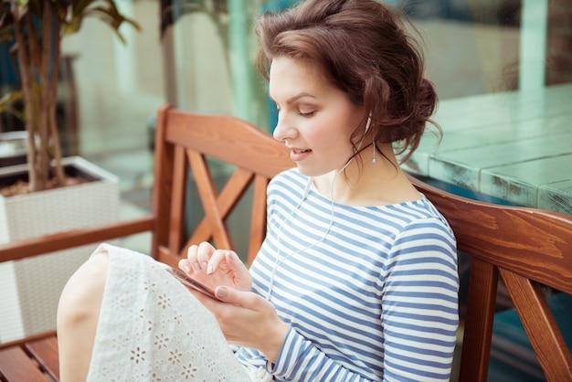Leuke hipster kaukasische tiener meisje met slimme telefoon en koptelefoon luisteren muziek, zittend op een bankje.