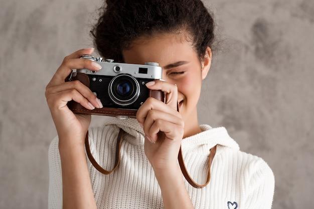Leuke hipster vrouw fotograferen op retro camera