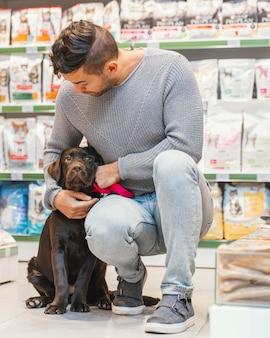 Leuke hond met eigenaar bij de dierenwinkel