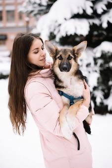 Leuke hondzitting op de handen van een meisje en het bekijken camera in de sneeuwwinter