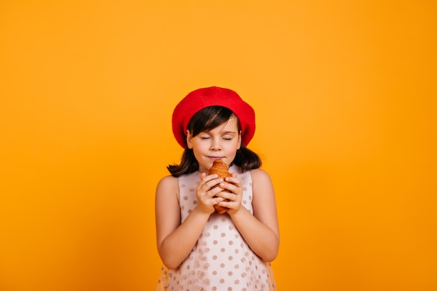 Leuke hongerige jongen die croissant eet. donkerharige meisje geïsoleerd op gele muur.