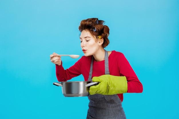 Leuke huisvrouw ruikt en proeft warme zelfgemaakte soep in de keuken