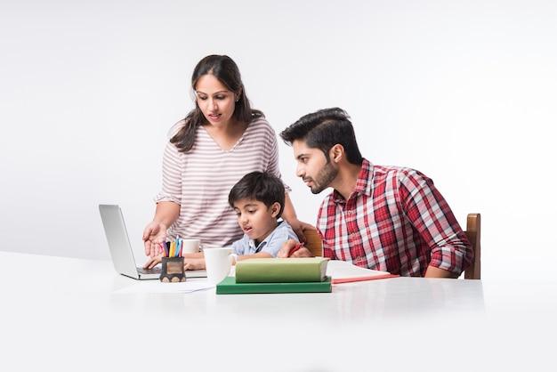 Leuke indiase jongen met vader en moeder die thuis studeren of huiswerk maken met laptop en boeken - online scholingsconcept