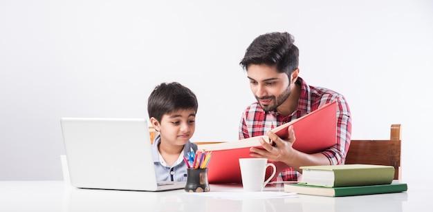 Leuke indiase jongen met vader of mannelijke leraar die thuis huiswerk maakt met laptop en boeken - online scholingsconcept Premium Foto