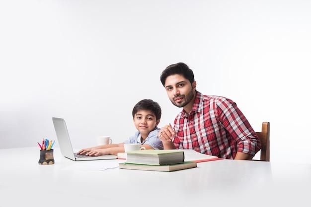 Leuke indiase jongen met vader of mannelijke leraar die thuis huiswerk maakt met laptop en boeken - online scholingsconcept