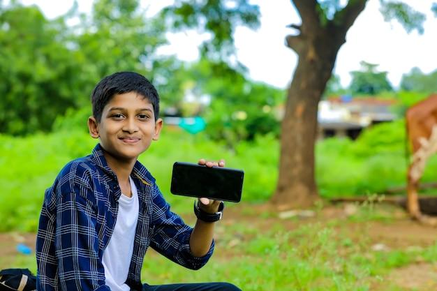 Leuke indiase schooljongen die online op smartphone thuis studeert
