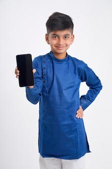 Leuke indische kleine jongen die het slimme telefoonscherm op wit toont