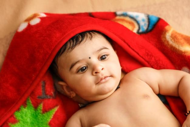 Leuke indische kleine jongen die op bed speelt