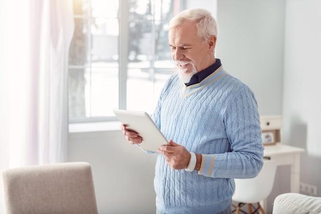 Leuke inhoud. knappe oudere man die in het midden van de woonkamer staat en van de tablet leest terwijl hij vrolijk lacht