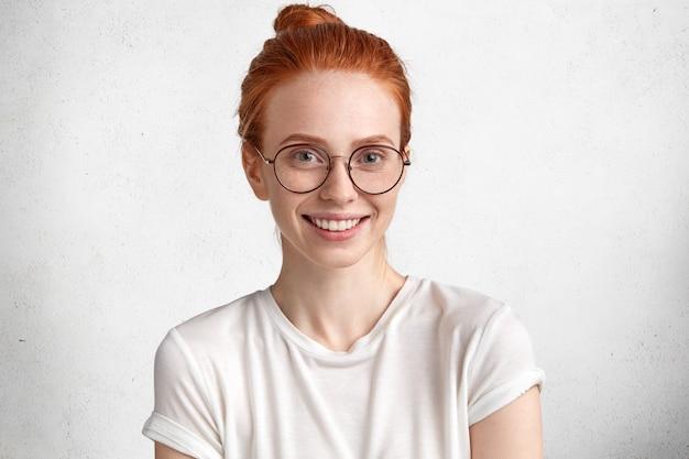 Leuke intelligente roodharige vrouwelijke student in ronde bril, verheugt zich met succes geslaagd voor examen in vreemde talen